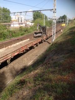 Vue du train avec la pelle sur le train de travaux pour répartir les déblais extraits par la pelleteuse