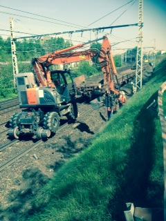 Vue du train de travaux sur la voie 1 bis avec la pelleteuse qui charge les gravats de la piste